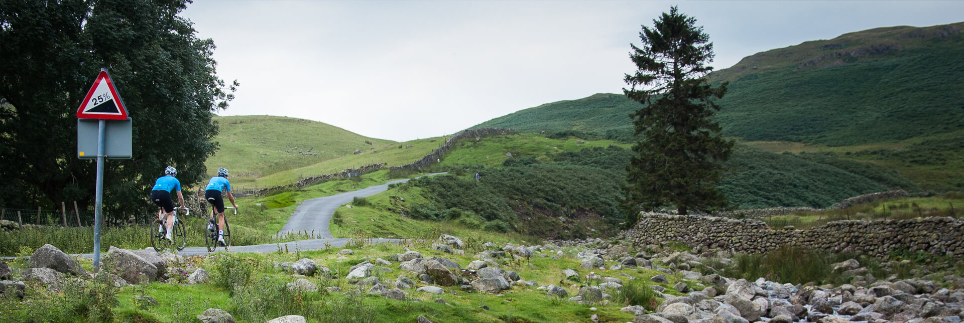 Three Peaks Cycle Challenge. Couple cycling up green English mountain