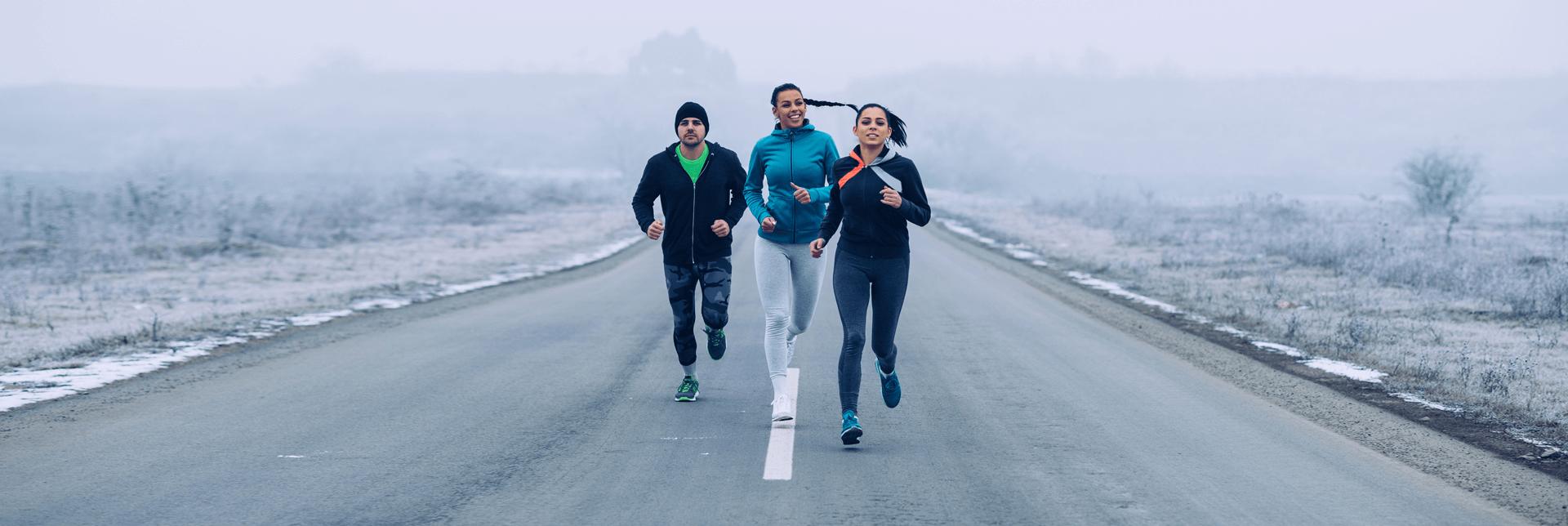Ladies and men enjoying running outdoors in winter